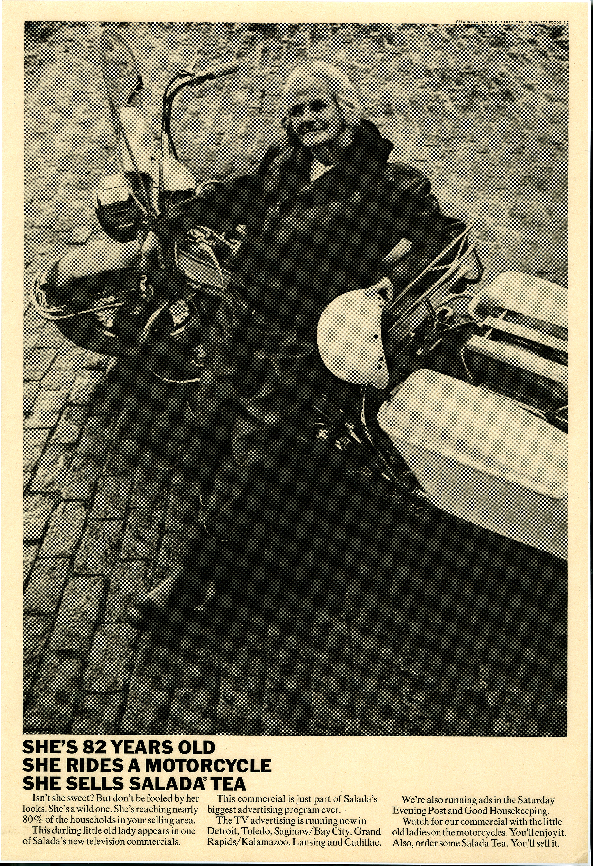 Black and white photograph of an elderly woman in a leather jacket leaning against a motorcycle.
