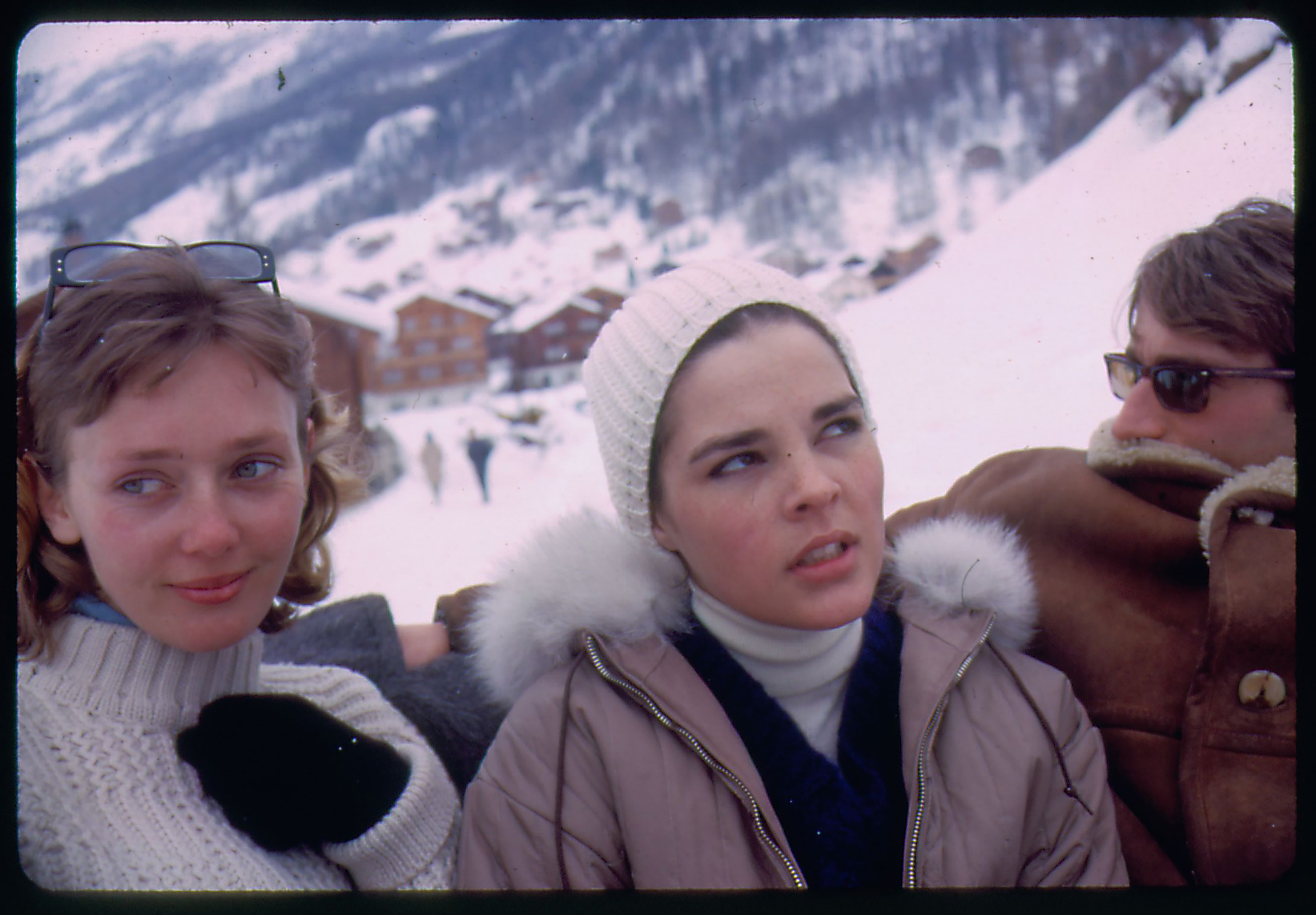 Candid color portrait of two women (one of them Ali MacGraw) and a man with a ski chalet in the background.