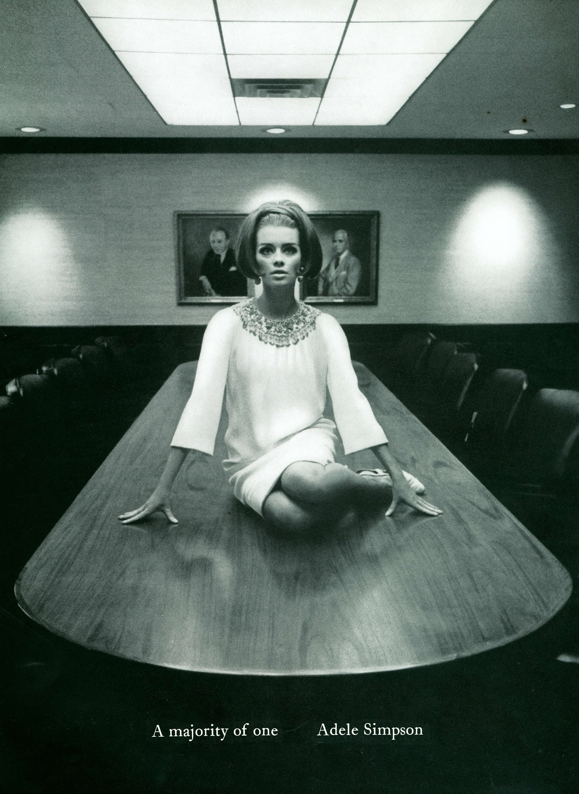 Black and white photo of a woman sitting on a a table in an empty conference room.