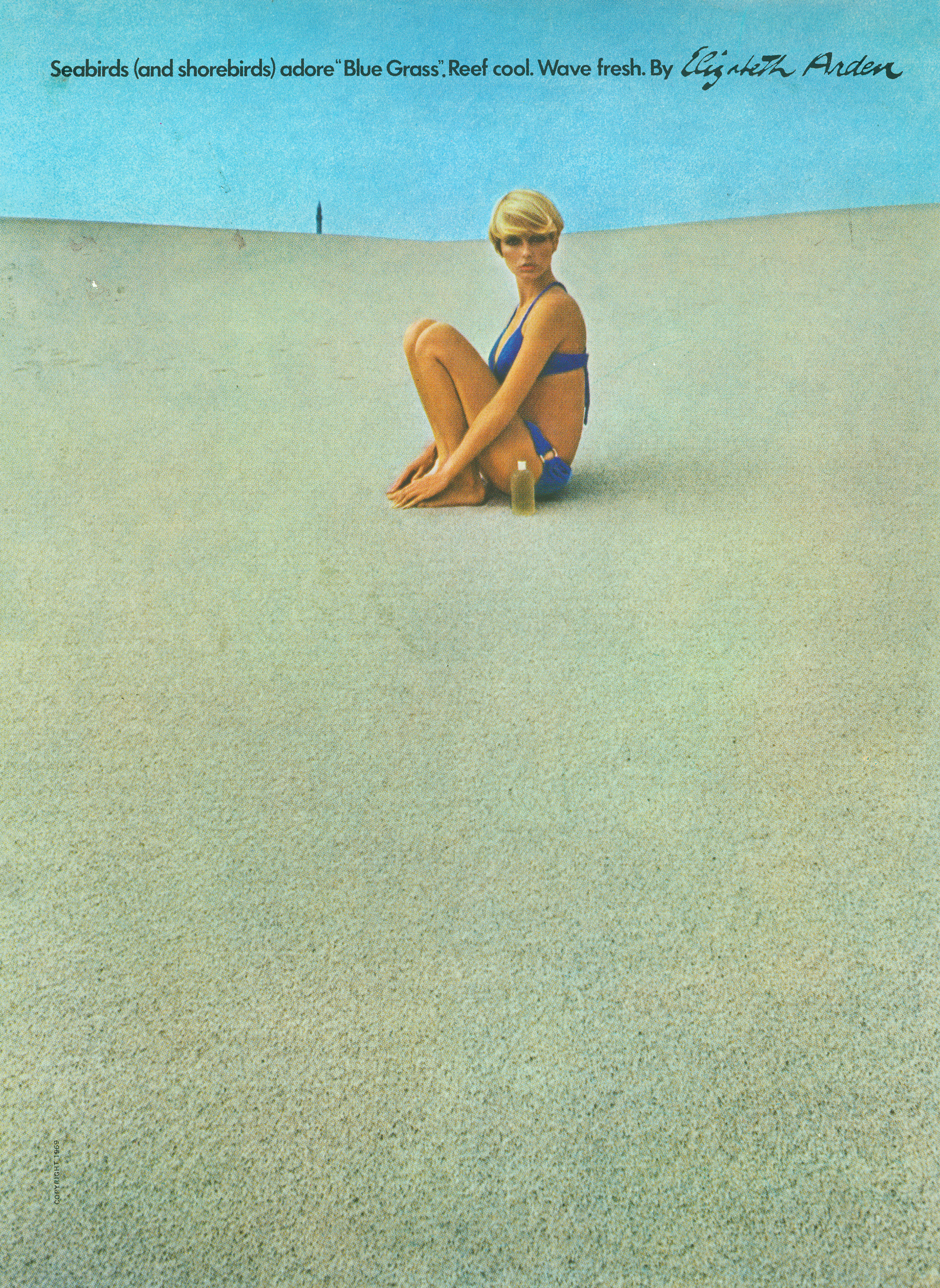 Color photo of a woman in a bikini sitting on a sand dune and looking at the viewer.