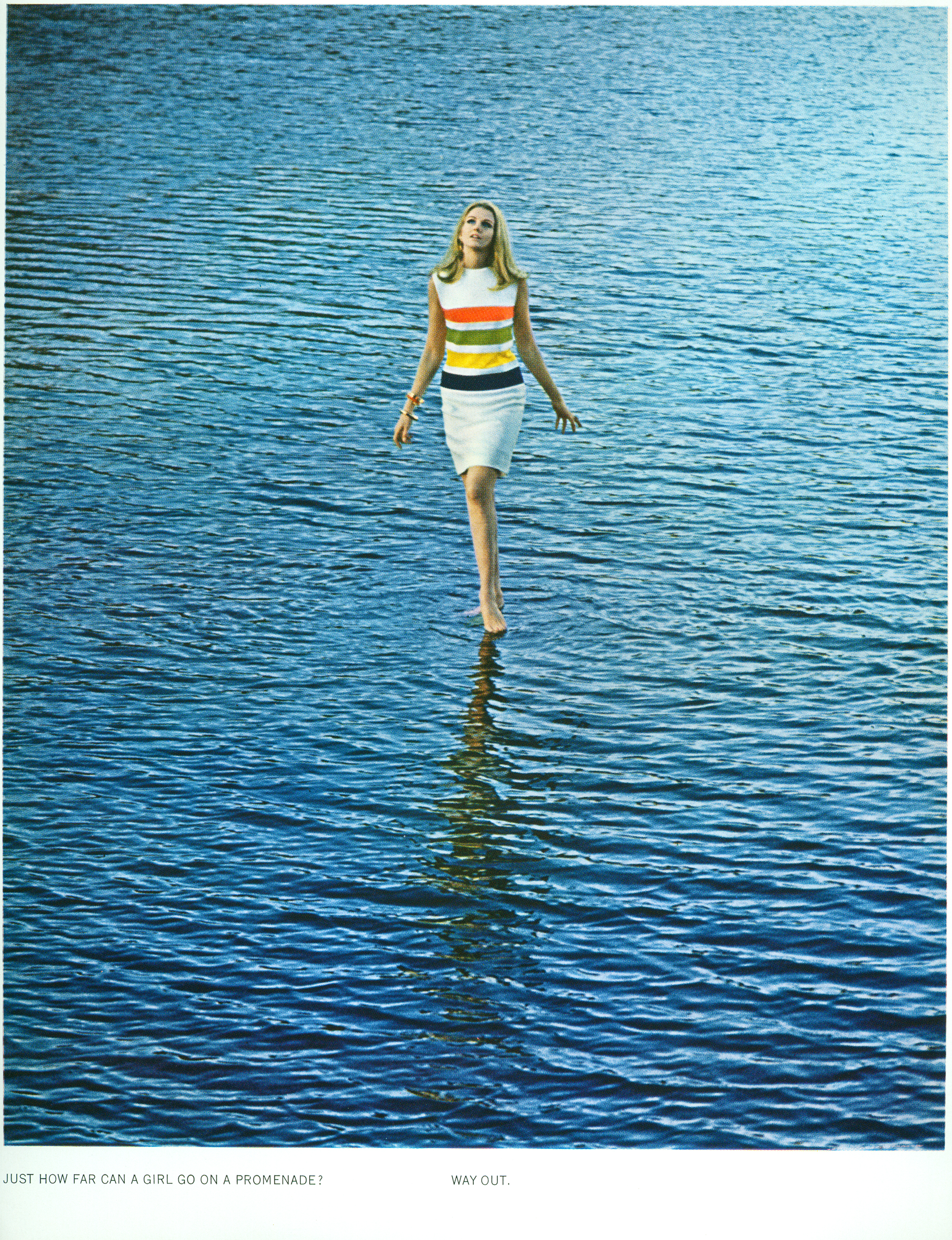 Color photo of a woman in a dress with four large orange, yellow, green, and blue stripes walking on water.
