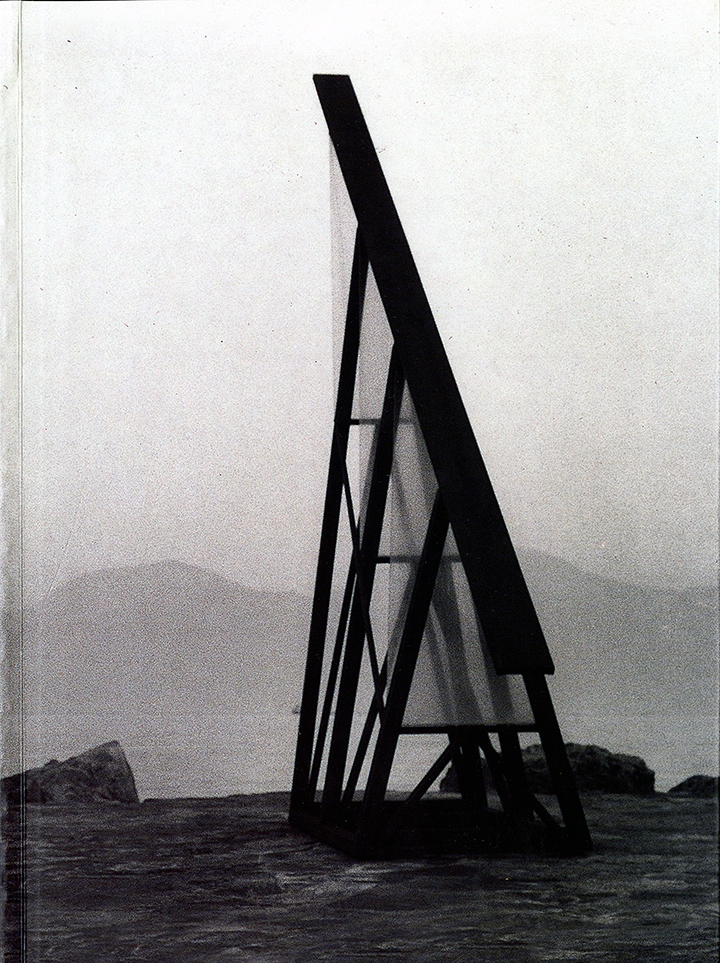 Black and white photo of a  triangular, ship-like structure near water. Mountains are visible in the distance.