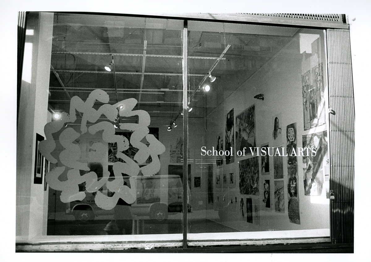 Black and white photograph of the Visual Arts Gallery as seen through a window. The SVA logo is on one of the panes of glass.