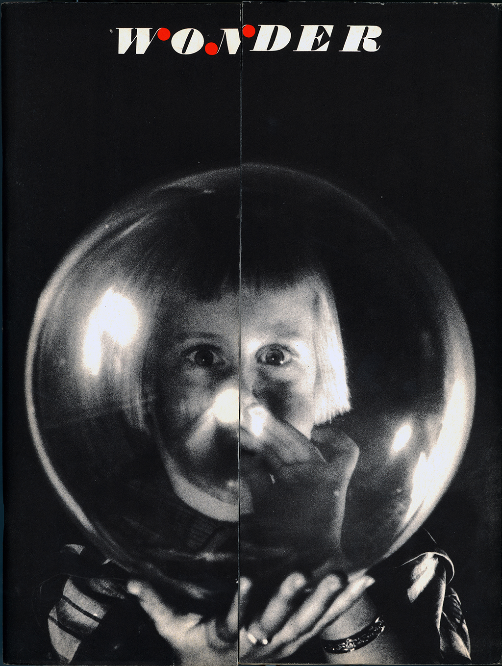 "A black-and-white photograph of a person touching a transparent sphere held up to their face, between them and the camera. Above them the word ""Wonder"" in white type with red ball serifs on the ""w"" and the ""n."""