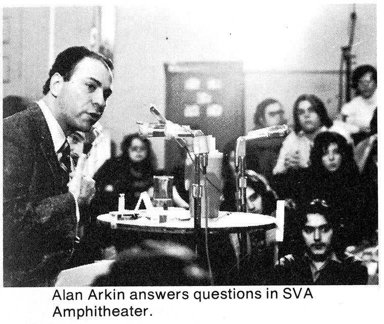 Arkin sitting at a table speaking into a microphone while students look on
