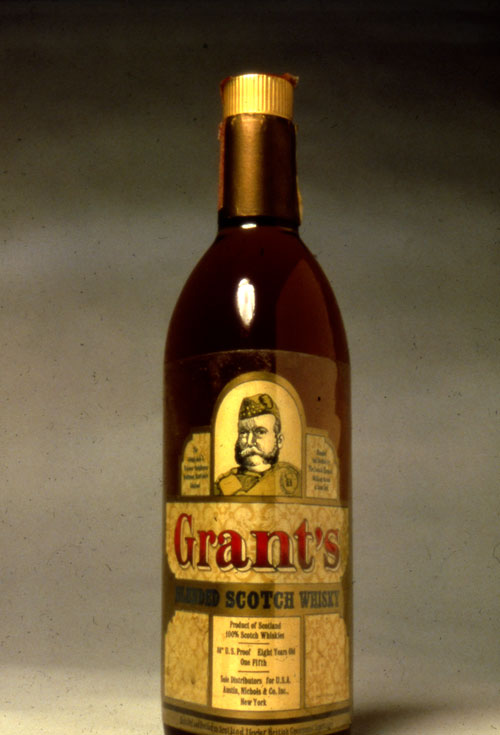 "A photo of  sealed brown alcohol bottle. The cap is gold and the label of the bottle is a dull gold color. In the middle on the top of the bale is a illustration of an old bearded army man. Underneath the illustration in big red-black gradient text is the product name, ""Grant's"". In a plain gold banner underneath is ""Blended Scotch Whisky"" in a slightly smaller thick bold black text."