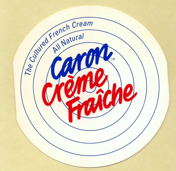A photo of Circular white card with thin blue lines on it resembling a target. Text reads in blue and red: The Cultured French Cream, All Natural, Caron Crème Fraîche.  Caron Crème Fraîche is in a bold cursive font.
