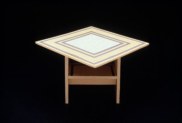 Photograph of a striped table with a chair visible underneath it