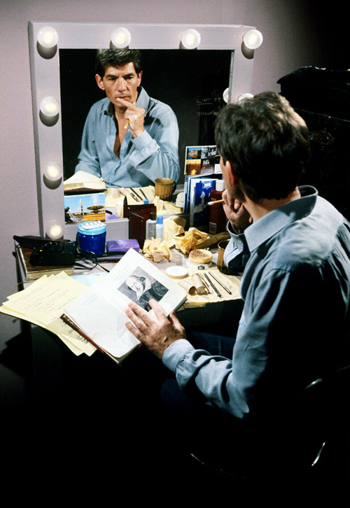 Photo of Ian McKellen behind the stage, practicing in front of a messy desk and mirror.
