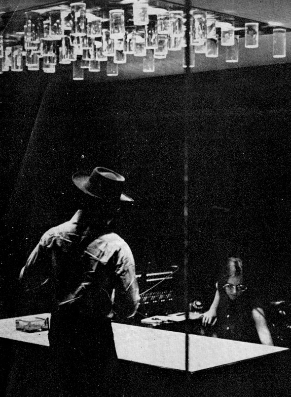 Black and white photograph of mid-century agency; a man in a hat approaches a woman at her desk underneath an expressionistic light fixture in the reception room.