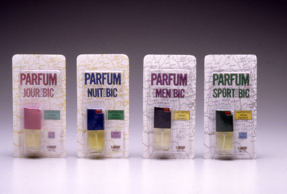 A photo of 4 packages of tiny perfume bottles. All packages has a white background with black outlines of a map with the perfume on the bottom right. Above the perfume is thin bold text reads the perfume's name, each package has a different color