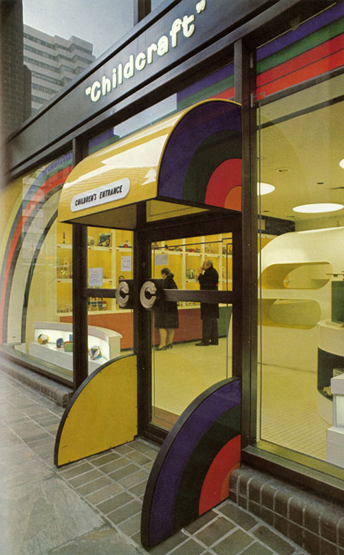 A close-up photo of the entrance of the location. The is two sets of doors, one for entering and one for exiting. The entrance has a bright yellow rigid storefront awning. On the side of the awning is a quarter circle rainbow pattern. There is a pair of small quarter-circle rainbow walls on the sides of the entrance door. You can see in the inside, two adults are looking at the cubbies that is filled with toys and other kid-like things.