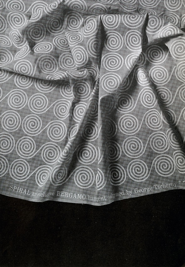"A photo of a grey thin cloth that has patterns of white circular spirals. At the bottom of the cloth ""SPIRAL an exclusive BERGAMO handprint design by George Tscherny"" is printed in white text. The cloth is scrunched in the middle and is not covering the whole image. Below the cloth is a black space."
