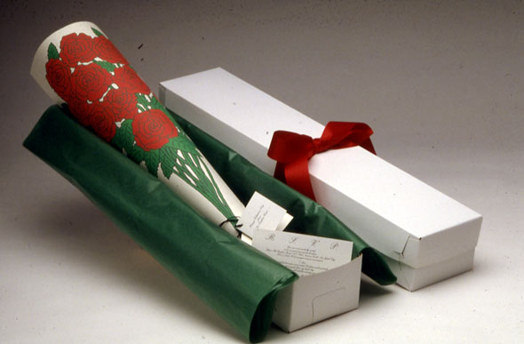 A white pencil box containing a rolled sheet of a paper, displaying a rose bouquet print. The box interior is layered with green wrapping paper.