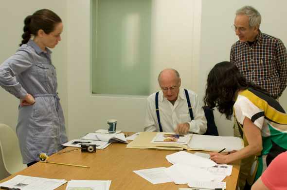 A photo of 4 people gathered around a table that has paper scattered. James McMullan is seated, in the middle of everyone who is standing. He is looking over his past work.