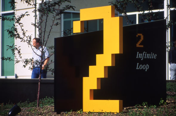 "A pixelated, yellow-orange ""2"" typography displayed outside a building entrance. Titled ""Infinite Loop""."