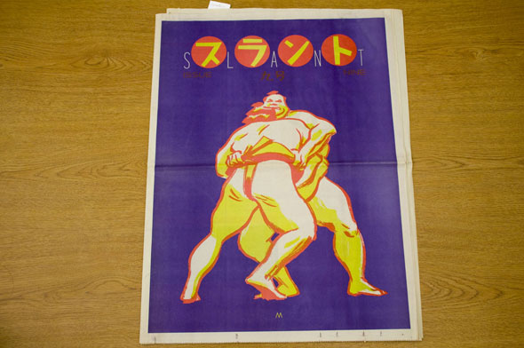 "A newspaper for ""Slant"". The front page is two sumo wrestlers wrestling in a bright blue background. The Sumos are colored white and yellow with a orange outline. Above the sumo is yellow Japanese calligraphy in small orange circles. Next to each circle are thin white letters that spell out ""Slant""."