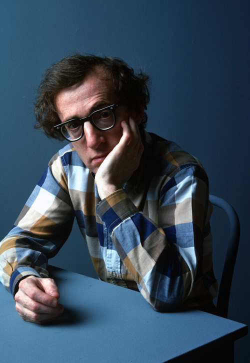 Photo Portrait of Woody Allen, seated in a chair and leaning against a vacant desk.