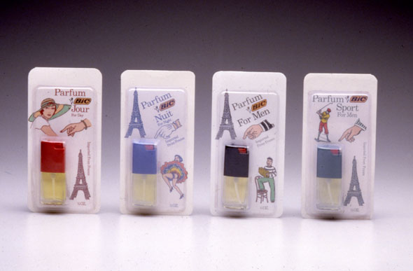 A photo of 4 packages of tiny perfume bottles. All packages have a white background with 3 small illustrations surrounding the perfume. They all have an Eiffel tower, a hand and a drawing that corresponds to the perfume's targeted audience (i.e. a woman's hand for the woman's perfume, a man's hand for the men perfume, a golfer for the sport perfume, etc)