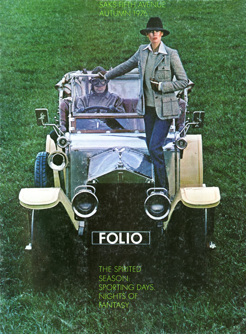 Color photo of a woman in a hat and blazer standing on top of a 1930's convertible car being driven by a man with goggles in a green field.