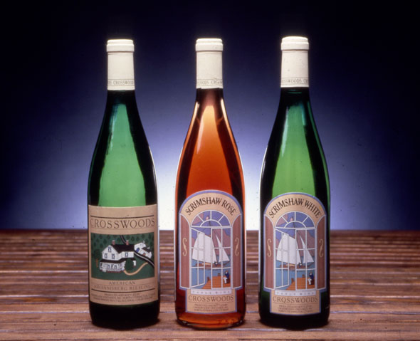 "A photo of 3 wine bottles. The leftmost green bottle is 'Cross Woods' Wines. The label is an illustration of a white suburban house on a green field. The middle clear bottle  is "" Scrismshaw Rose"". The label is an illustration of a wooden boat with white sails viewed from insides a window. The rightmost green bottle is ""Scrimshaw White"". The label is an illustration of a wooden boat with white sails viewed from insides a window."