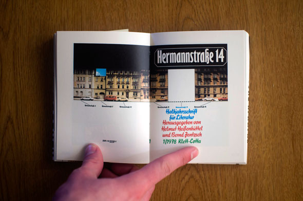 Flipbook opened to show a spread depicting colorful block text and a building