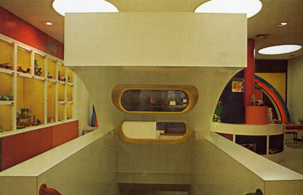A photo of a a white geometric-like staircase housing inside the location. Its behind the front desk. It has a red railing on the left and a blue railing on the right. The house has a curved top that has two wide holes that serves as shelfs for the front desk. You see the cubbies of toys on the left with rainbow striped colored walls.