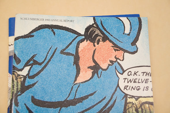 A photo of the cover of an annual report. The cover is water illustration of a working man with a blue hardhat on. He have a sky blue shirt on and has a speech bubble that goes off the page. The man is outlined with thick black ink.