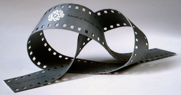 "A photo of a film strip shaped into a pretzel form. At one end ""The DUSTY Award"" is printed in black text. In the middle of the film strip is the the School of Visual Art's logo with "" School of VISUAL ARTS"" printed in black text."