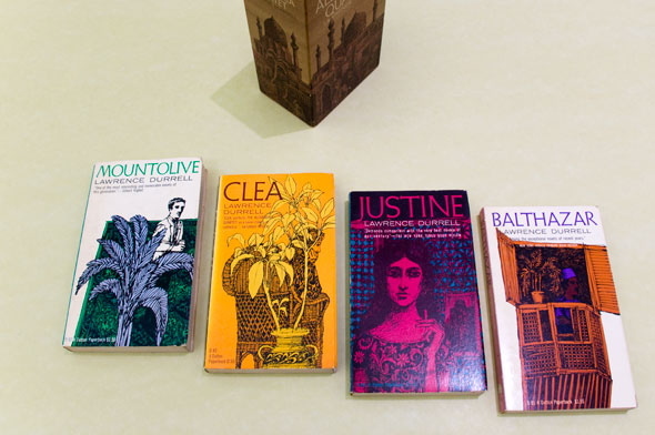 "A photo of 4 books. From left to right; ""Mountolive"", ""Clea"", ""Justine"", and ""Balthazar"". Each book cover has the title on the top in thin text, the color of text correspond to the colors used on their covers. Each book has vibrant saturated colors and sketchy drawings that emphasizes the details."