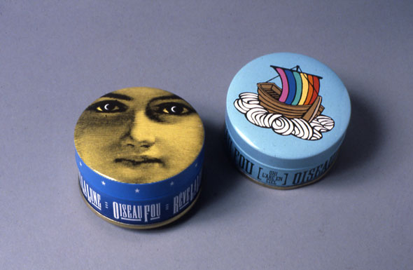 "Two small, circular tin containers. The left is navy blue with a woman's face on it's lid, the right is light blue with a boat and rainbow sails. Both tins have ""Oiseau Fou"" written on the sides."