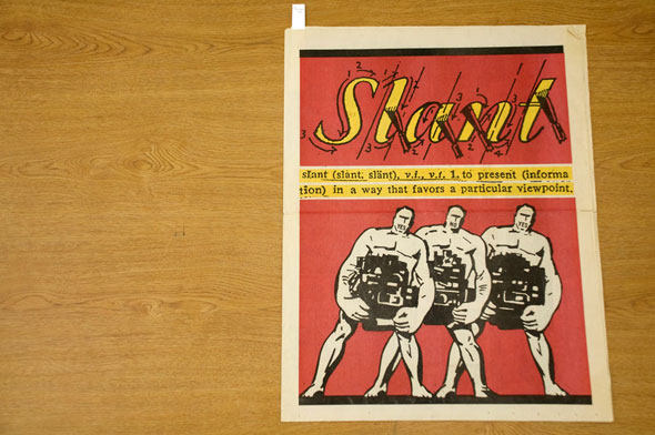 "A front cover of a news paper. On a red background three white muscled men each carry a heavy machine. They struggle carrying and slant a bit to the right. Above them in yellow cursive text is the titles of the news paper,"" Slant"". The Title has arrows and arrows on each letter, it's designed to look like a how-to-write-cursive letter. Below the title in a thin yellow background is the definition of, ""Slant"". ""to present (information) in a way that favors a particular viewpoint""."