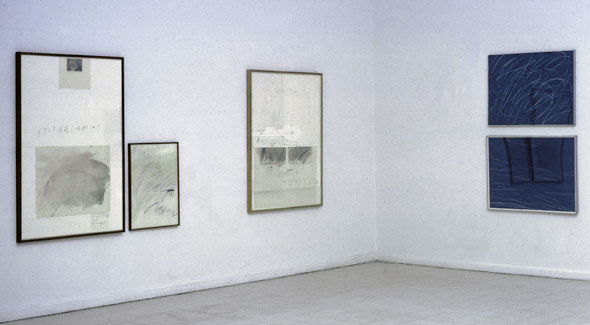 Color photo of the interior corner of an art gallery, displaying four paintings