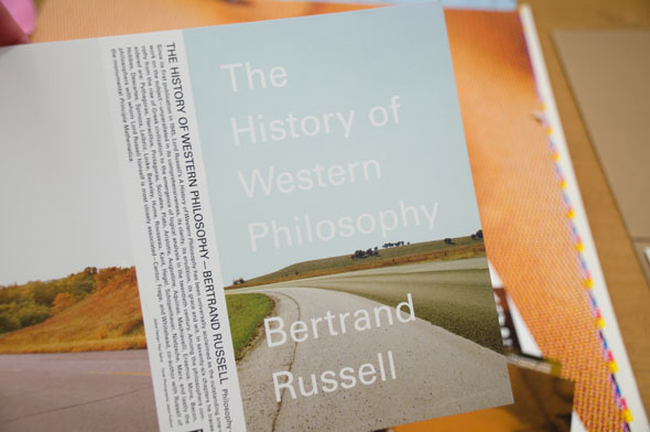 "A photo of a book jacket for ""The History of Western Philosophy"" by Bertrand Russell.The title and author's name is written in a thin white front. The front is a picture of an empty road in plain calm field."