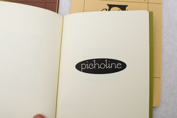 "Green book opened to reveal a black and white logo reading ""picholine"" in a delicate font"