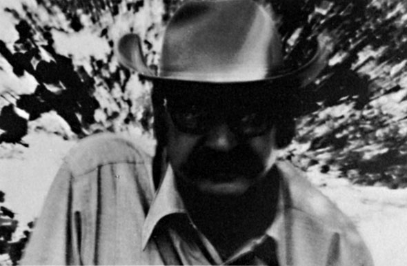 Black and white photograph of a man facing the camera, his face obscured by dark sunglasses and a cowboy hat