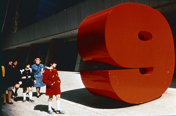 Five people looking at a large red sculpture of the number nine.