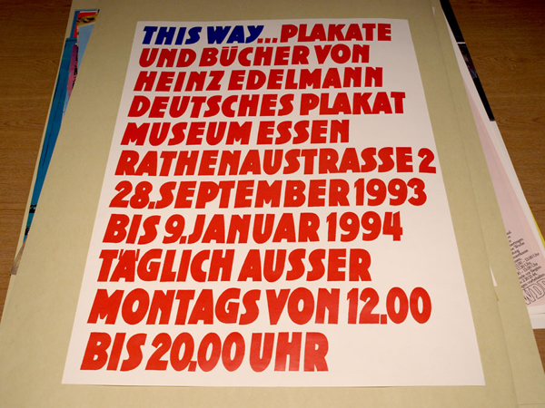 Poster for Edelmann exhibition depicting red and blue block text against white background.