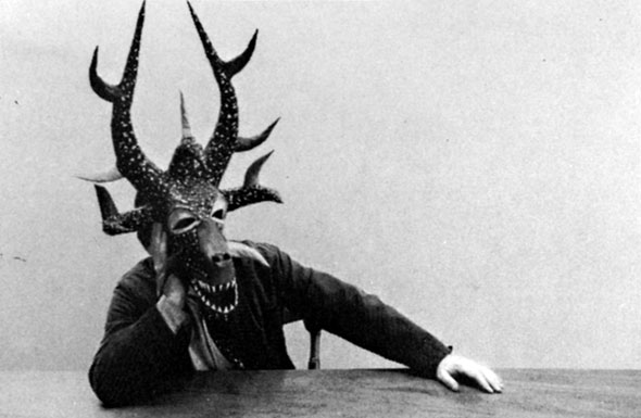 Black and white photograph of someone wearing a complex, dragon-like mask with large horns