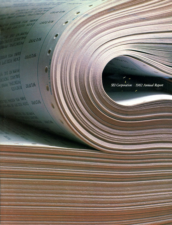 "A photo of a bundle of paper. The top half of the bundle is folded over. Between the fold is ""SEI Corporation. 1982 Annual Report"" in white text."