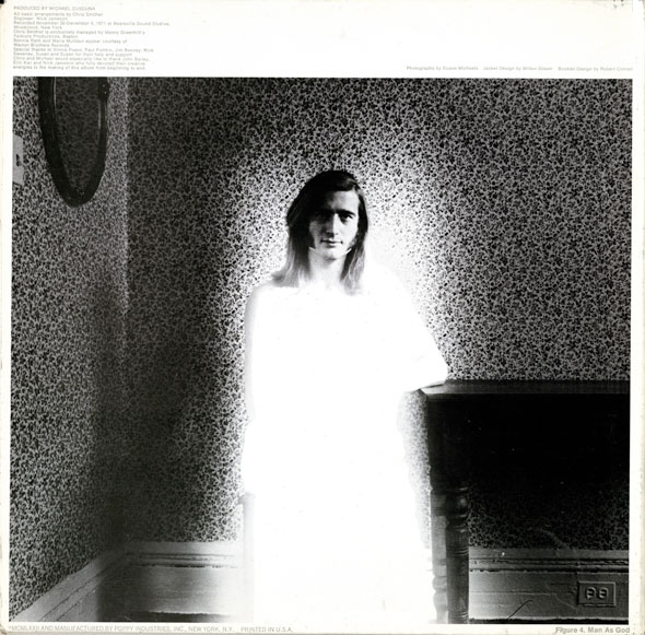 Black and white photo of A longhaired man sits by a piano is a wallpapered room; his body is engulfed in bright white light. It's the same room and man as the previous pictures.