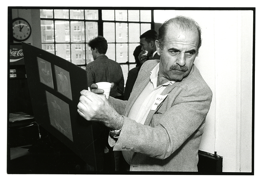 Ed Benguiat holding a poster board and cup
