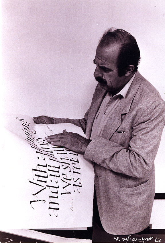 Ed Benguiat looking at sheet of hand lettered words