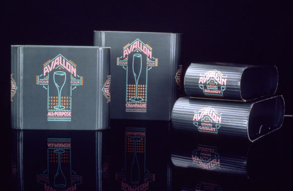 "A photo of a product. There are four cardboard boxes. Two are standing up right on the left side the other two are stacked on right side. The upright boxes have similar design for ""Avallon"" The design is similar to a Las Vegas neon sign with the neon blue, pink, and yellow colors and the design of a blue wine glass with the Product name ""Avallon"" in neon oink grand text. The stacked boxes have a smaller version of that design without the wine glass."