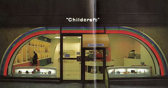 "A photo of the ""Childcraft"" location from the outside. It has an large windows, so you can see inside. There is a illuminated circular motif near the windows that looks like a rainbow. The entrance door has a bright yellow storefront awning and near the door is a quarter circle wall walkway. ""Childcraft"" on the top of the location in a simple white illuminated sign. The lettering is minimalistic and is not in all caps. Inside you can see the brightly colored lobby that has cubbies on the wall and toys displayed in front of the window."
