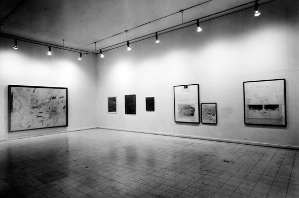 Black and white photo of the interior of an art gallery, showing 7 paintings