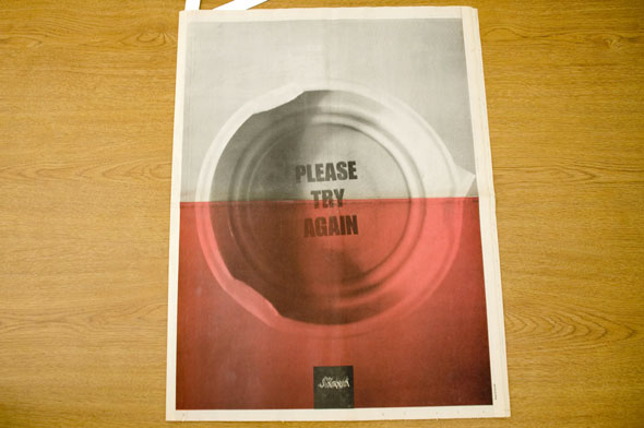 "A newspaper for ""Slant"". The front/back cover is a photo of the underside of a bottle cap that has ""Please Try Again"" in bolded black text. The half of the image has a light red hue overlaid on it."