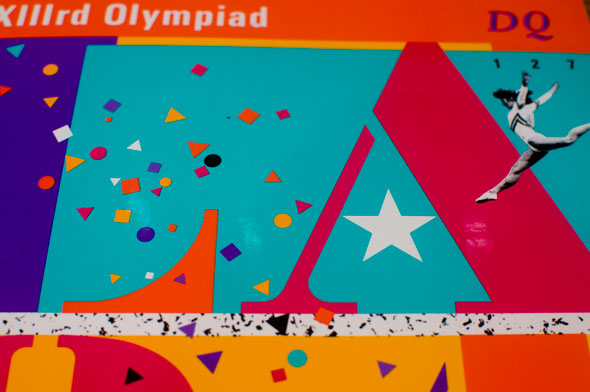Closeup photo of a bright colorful magazine header; confetti-like shapes, a small black and white gymnast, a star and the letters LA are visible.