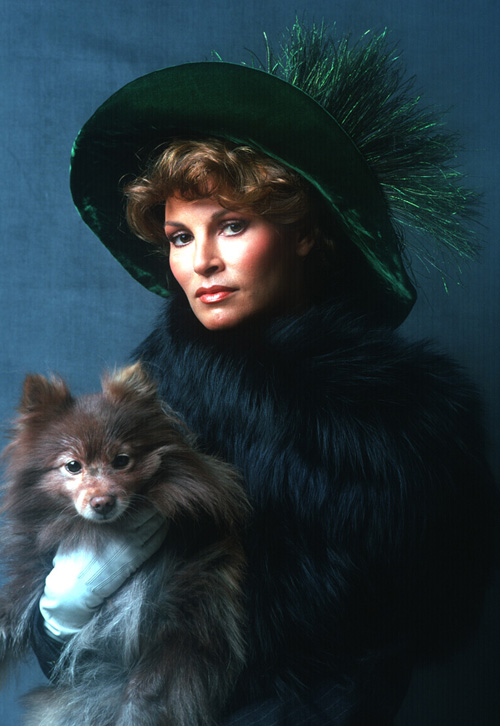 Photo Portrait of Racquel Welch wearing a green floppy hat, faux fur, and holding a brown Pomeranian dog.