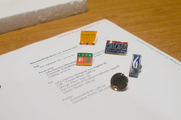 A photo of a collection of colorful enamel pins on a table.